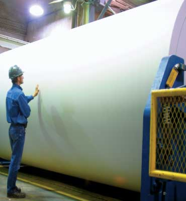 Man standing by a roll of paper