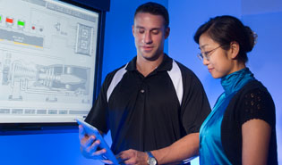 A man and a woman looking at tablet in front of control system graphics